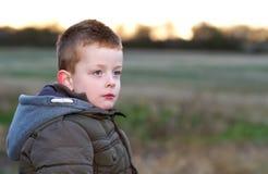 Muchacho joven triste en un campo Fotografía de archivo libre de regalías