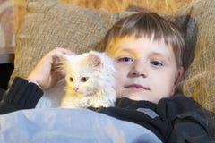 Muchacho joven y alegre con un gato blanco en el sofá que mira la cámara y que frota ligeramente el gato Imagen de archivo libre de regalías