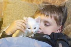 Muchacho joven y alegre con un gato blanco en el sofá que mira la cámara y que frota ligeramente el gato Fotos de archivo libres de regalías