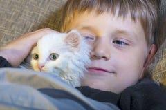 Muchacho joven y alegre con un gato blanco en el sofá que mira la cámara y que frota ligeramente el gato Foto de archivo