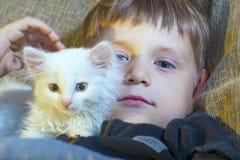 Muchacho joven y alegre con un gato blanco en el sofá que mira la cámara y que frota ligeramente el gato Fotografía de archivo libre de regalías