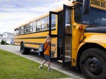 Muchacho joven y autobús escolar amarillo Imagen de archivo libre de regalías