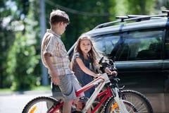 Muchacho joven y muchacha que toman una rotura de montar en bicicleta Foto de archivo libre de regalías