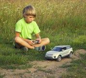 Muchacho jugado con un coche radio-controlado foto de archivo