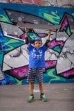 Muchacho juguetón feliz que sostiene su monopatín Imagen de archivo libre de regalías