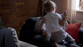 Muchacho juguetón que se sienta con la madre embarazada en la butaca almacen de metraje de vídeo