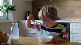 Muchacho lindo 4 años que comen copos de maíz del desayuno con leche en la tabla en casa almacen de metraje de vídeo