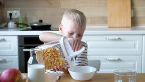 Muchacho lindo 4 años que comen copos de maíz del desayuno con leche en la tabla en casa almacen de video