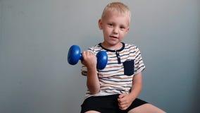 Muchacho lindo 6 años que hacen ejercicios con pesa de gimnasia en fondo gris almacen de metraje de vídeo