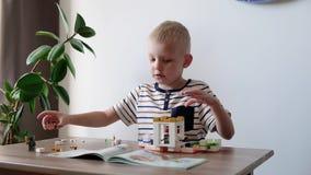 Muchacho lindo 6 a?os que juegan con los ladrillos pl?sticos coloridos del juguete en la tabla en casa almacen de metraje de vídeo