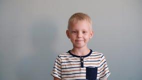 Muchacho lindo 6 años que juegan mirando la cámara y la sonrisa Fondo gris metrajes