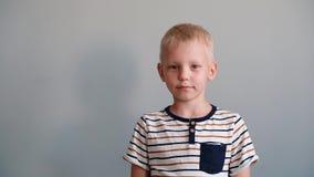 Muchacho lindo 6 años que juegan mirando la cámara y la sonrisa Fondo gris almacen de video
