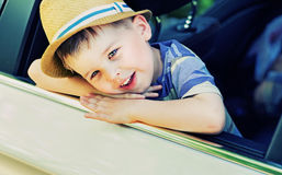 Muchacho lindo aburrido en el coche Foto de archivo