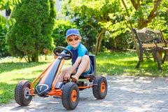 Muchacho lindo activo que se divierte con los coches de carreras del juguete Imagenes de archivo