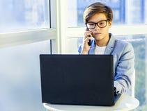 Muchacho lindo adolescente del negocio con el teléfono y el ordenador en oficina Fotos de archivo libres de regalías