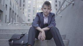 Muchacho lindo bien vestido pensativo que se sienta en las escaleras en la calle El muchacho está cansado y quiere ser apenas un  almacen de metraje de vídeo