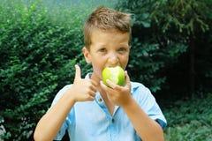 Muchacho lindo con Apple y los pulgares verdes para arriba Foto al aire libre Educación y concepto de la moda de los niños Foto de archivo