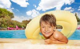Muchacho lindo con el anillo inflable de la nadada en la piscina Fotos de archivo libres de regalías