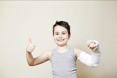 Muchacho lindo con el brazo quebrado Fotos de archivo