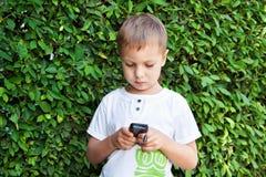 Muchacho lindo con el teléfono móvil Imagenes de archivo