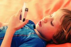 Muchacho lindo con el teléfono móvil Imágenes de archivo libres de regalías