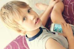 Muchacho lindo con el teléfono móvil Fotos de archivo libres de regalías