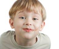 Muchacho lindo con la cara del chocolate Imagen de archivo