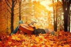 Muchacho lindo con la guitarra, mintiendo en la hierba en día soleado del otoño Fotos de archivo