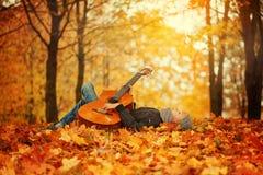 Muchacho lindo con la guitarra, mintiendo en la hierba en día soleado del otoño Imagen de archivo