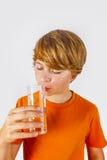 Muchacho lindo con las bebidas anaranjadas de la camisa Imagen de archivo libre de regalías