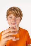 Muchacho lindo con las bebidas anaranjadas de la camisa Fotos de archivo libres de regalías