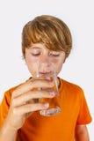 Muchacho lindo con las bebidas anaranjadas de la camisa Fotos de archivo