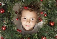 Muchacho lindo con las decoraciones de la Navidad Imagenes de archivo