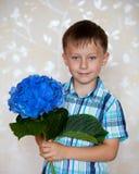 Muchacho lindo con las flores azules Foto de archivo libre de regalías
