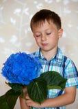 Muchacho lindo con las flores azules Fotografía de archivo libre de regalías