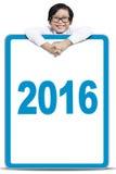 Muchacho lindo con los números 2016 en el tablero Foto de archivo