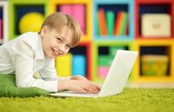 Muchacho lindo con un ordenador portátil Fotografía de archivo