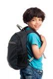 Muchacho lindo de la raza mixta con de la mochila la parte posterior encendido. Imagen de archivo libre de regalías