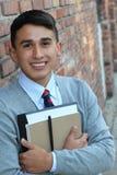 Muchacho lindo del adolescente en el alto uniforme escolar formal que celebra la sonrisa de los cuadernos Foto de archivo libre de regalías