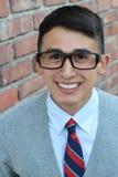 Muchacho lindo del adolescente en la alta sonrisa formal del uniforme escolar y de los vidrios Imágenes de archivo libres de regalías