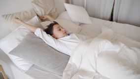 Muchacho lindo del adolescente que despierta por mañana Muchacho que estira en cama almacen de metraje de vídeo