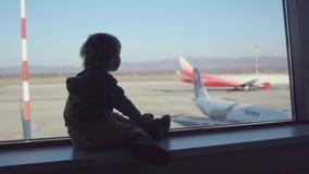 Muchacho lindo del muchacho del todler que espera un vuelo en aeropuerto almacen de metraje de vídeo