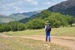 Muchacho lindo del niño con la mochila que camina en una pequeña trayectoria en montañas Caminar al niño imagen de archivo