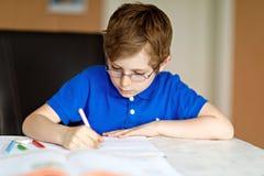 Muchacho lindo del niño con los vidrios en casa que hacen la preparación, escribiendo letras con las plumas coloridas Fotos de archivo libres de regalías