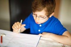 Muchacho lindo del niño con los vidrios en casa que hacen la preparación, escribiendo letras con las plumas coloridas Foto de archivo libre de regalías