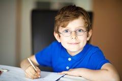 Muchacho lindo del niño con los vidrios en casa que hacen la preparación, escribiendo letras con las plumas coloridas Fotografía de archivo