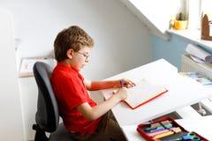 Muchacho lindo del niño con los vidrios en casa que hacen la preparación, escribiendo letras con las plumas coloridas Imagen de archivo