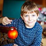 Muchacho lindo del niño que adorna el árbol de navidad con las bolas coloridas Imagen de archivo libre de regalías