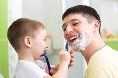 Muchacho lindo del niño que afeita a su padre en cuarto de baño Imagen de archivo