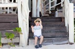 Muchacho lindo del niño que se sienta en las escaleras Foto de archivo libre de regalías